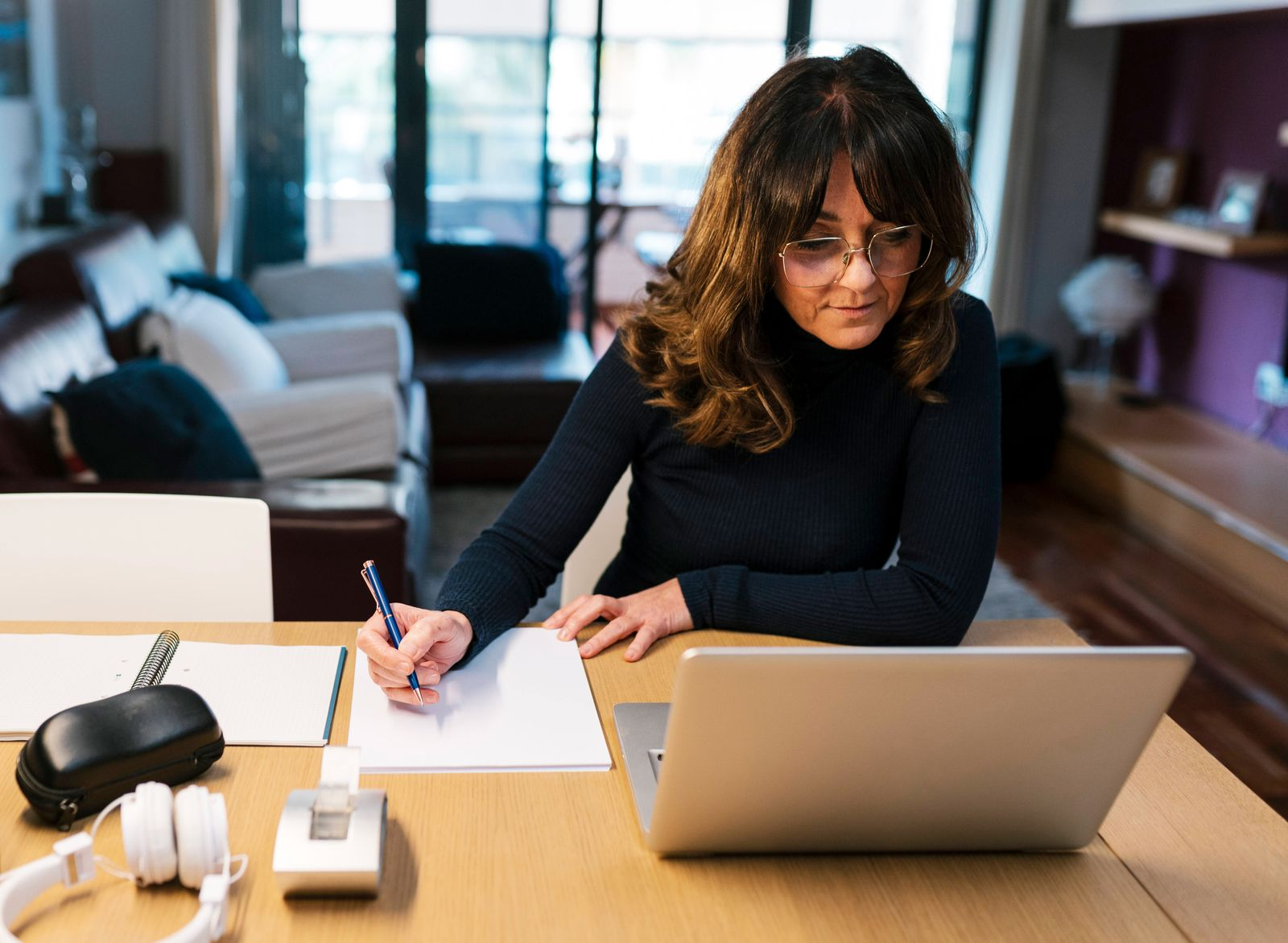 Mature woman writing in paper while sitting by laptop at home model released Symbolfoto property released EGAF02015