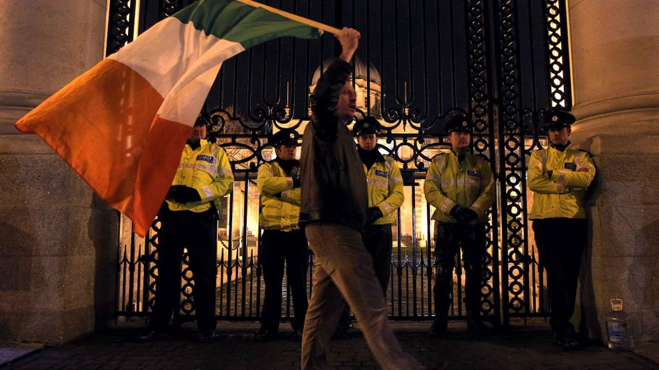 A protester waves a Irish flag outside the Irish prime minister's office in Dublin on Sunday: The EU and the IMF have agreed to a massive bailout for Ireland.
