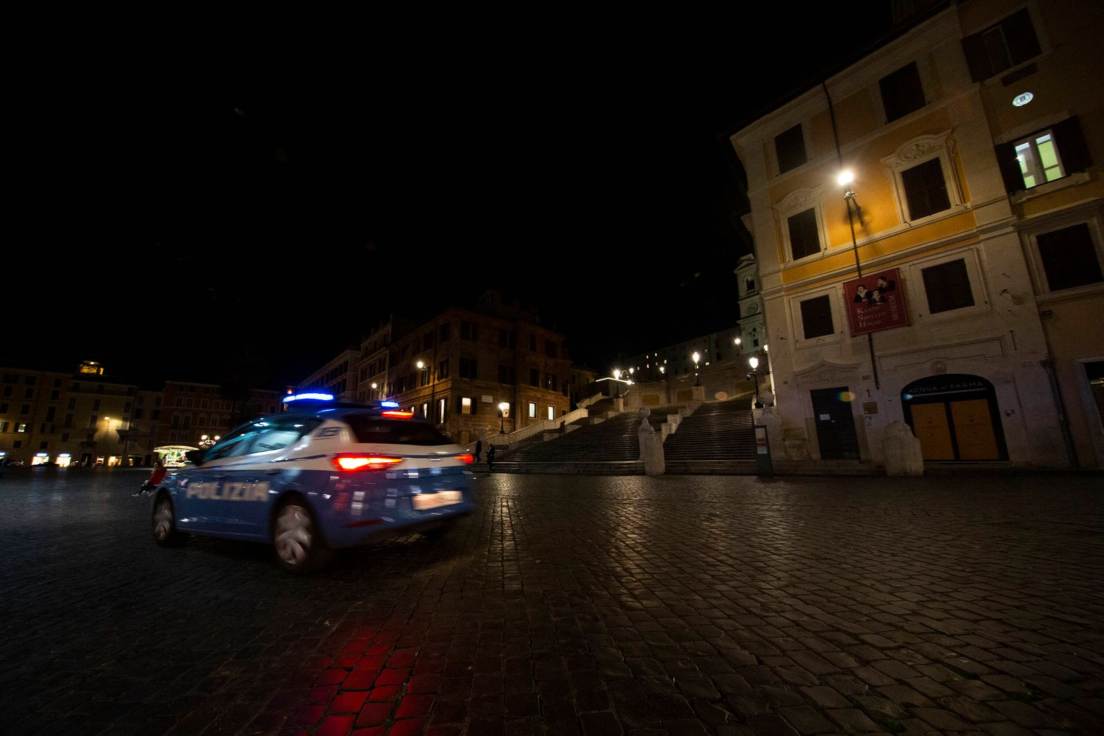 Italy in lockdown as coronavirus cases grows a police car passes in front of the Spanish Step in Rome in the evening bef
