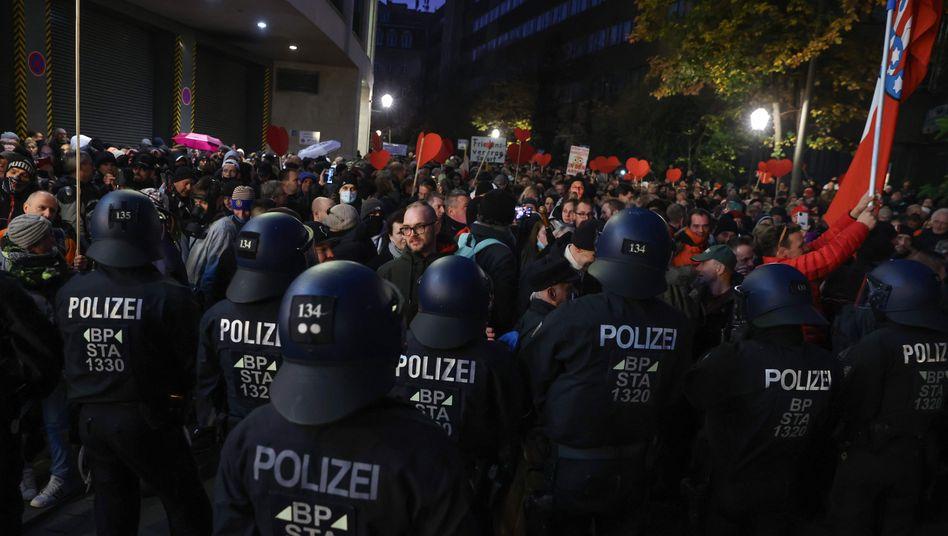 Polizisten vor einer Gruppe von sogenannten Querdenkern