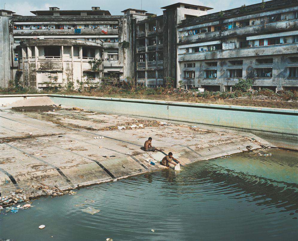 """Menschen waschen ihre Kleidung in dem Pool des ehemaligen Luxushotels """"The Grande"""" in Beira, Mosambik. Guillaume Bonn hat für seine Fotoserie """"Mosquito Coast"""" die ostafrikanische Küste bereist"""