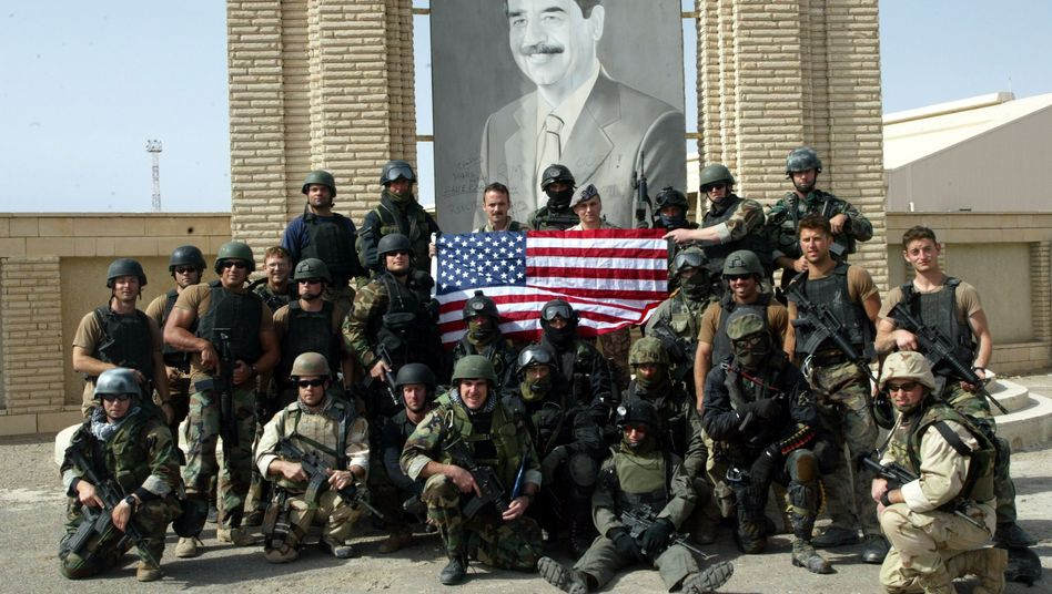 Polish special forces and US Navy Seals pose for pictures under a portrait of Iraqi President Saddam Hussein in the port of Umm-Qasr in southern Iraq in March 23, 2003.