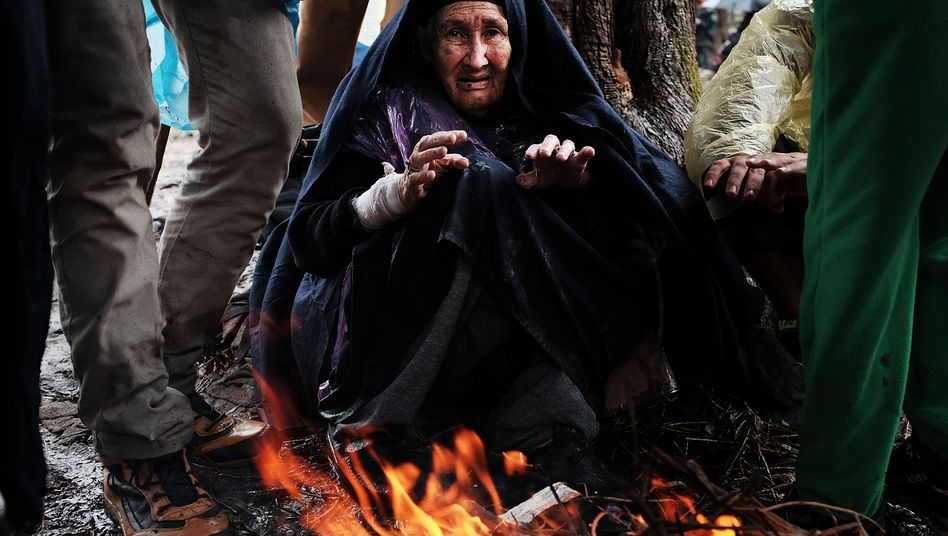 A 90-year-old warms herself by a fire at the increasingly overwhelmed Moria camp on the island of Lesbos on Oct. 23, 2015 in Mitilini, Greece.