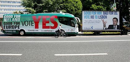 "A cyclist passes by a ""Yes"" for Lisbon Treaty bus and a ""No"" for Lisbon truck in Dublin, Ireland in June 2008."