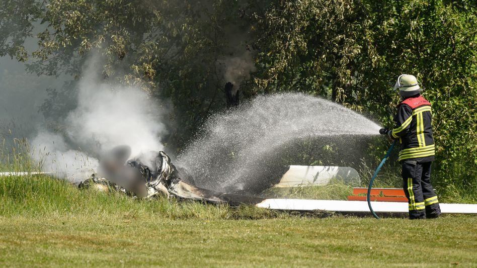 Ein Feuerwehrmann löscht an der Absturzstelle des Segelflugzeugs bei Fulda die letzten Glutreste