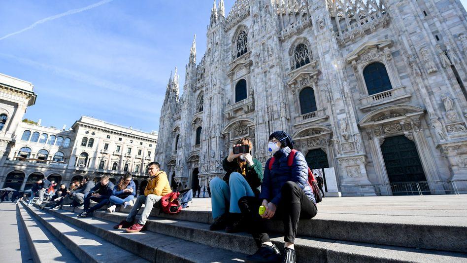 Touristen mit Schutzmaske vor Mailänder Kathedrale