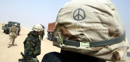 A US soldier with a peace symbol on his helmut: A visit by Germany's foreign minister to Iraq is long overdue.