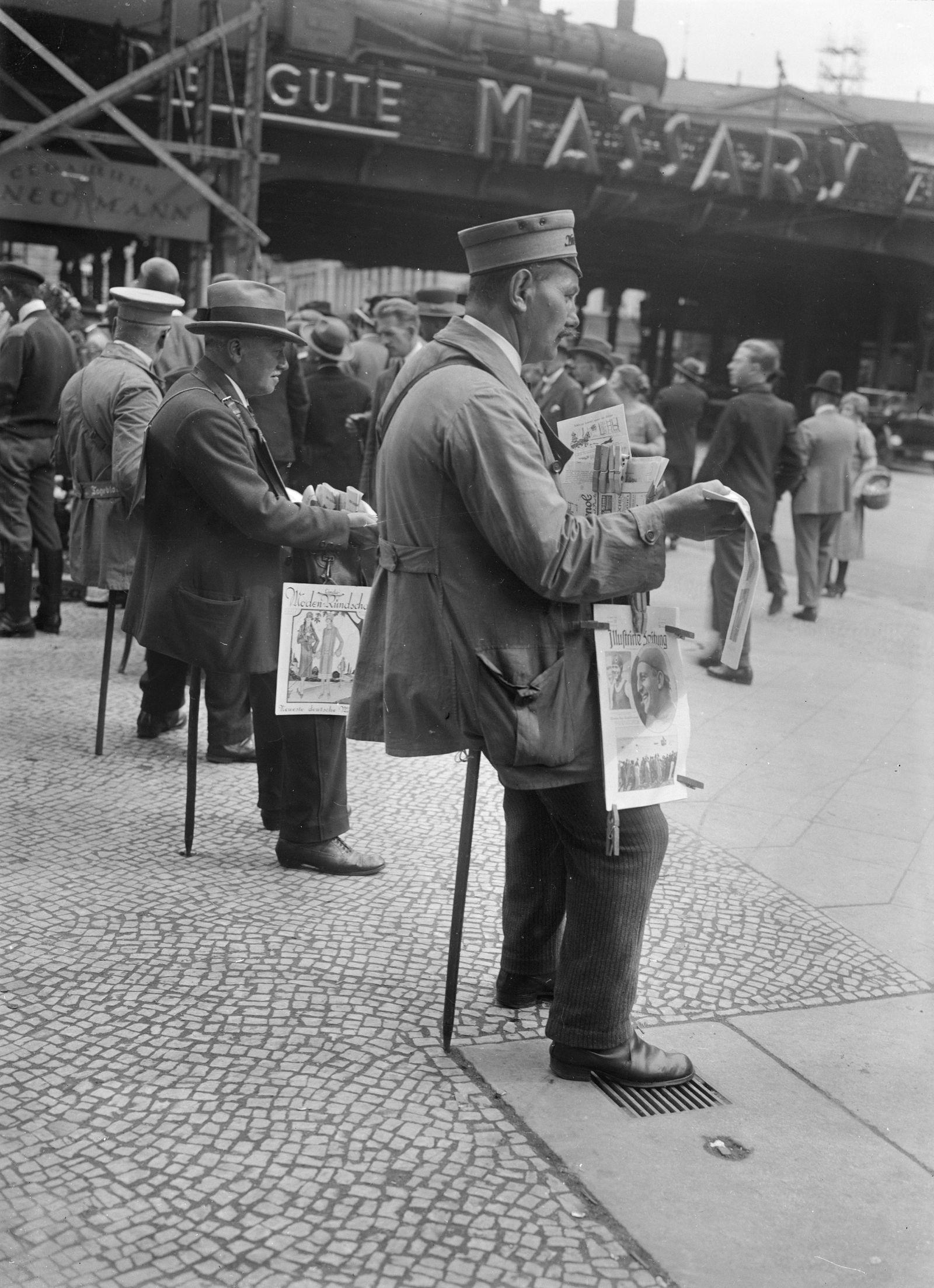 Zeitungsverkäufer auf Sitzstöcken am Bahnhof Alexanderplatz