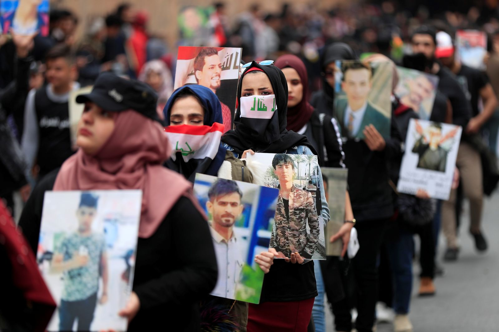 University students carry pictures of demonstrators who were killed during ongoing anti-government protests in Baghdad