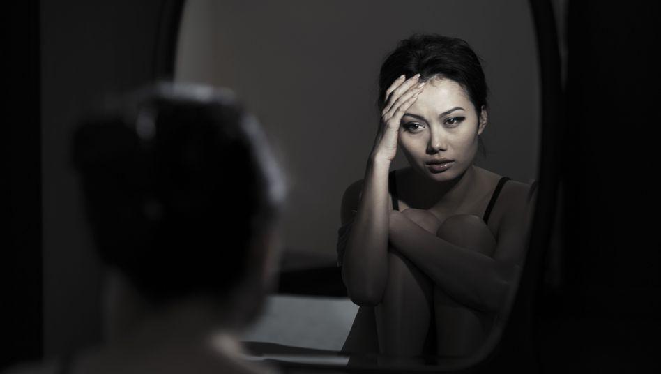 Junge Frau vor dem Spiegel: Die Unzufriedenheit mit dem eigenen Aussehen treibt Betroffene in die soziale Isolation