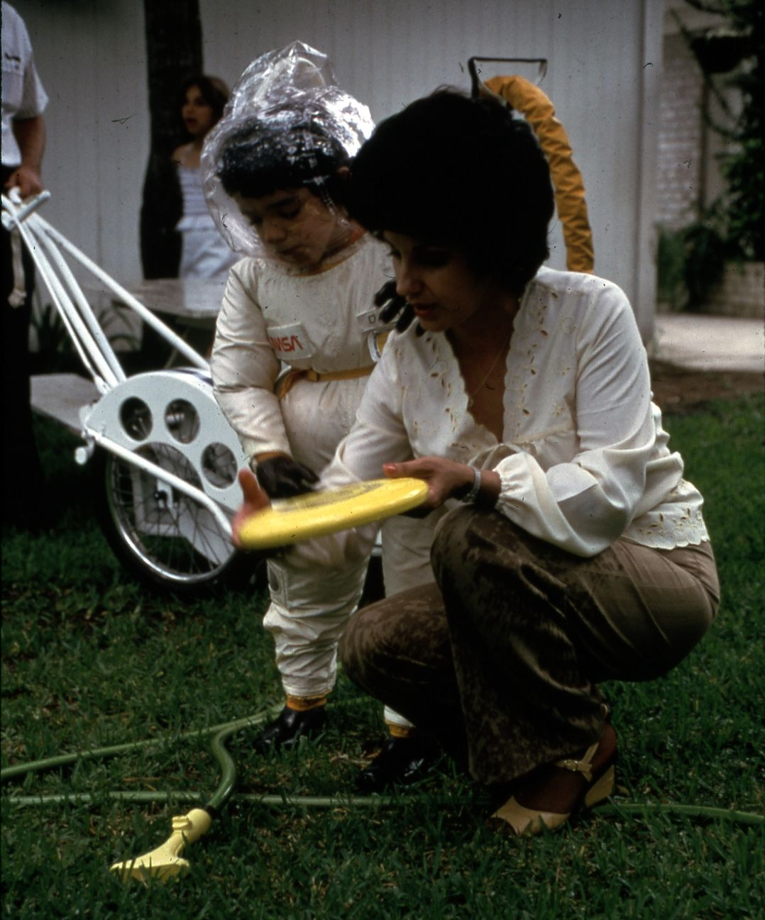 david in space suit outside with mom