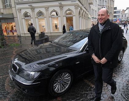 Transport Minister Wolfgang Tiefensee stands next to his official car. The Green Party wants politicians to switch to smaller cars and bikes.