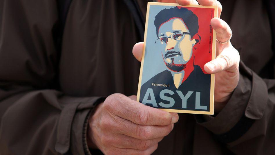 Ein Demonstrant zeigt ein Bild mit Snowdens Konterfei