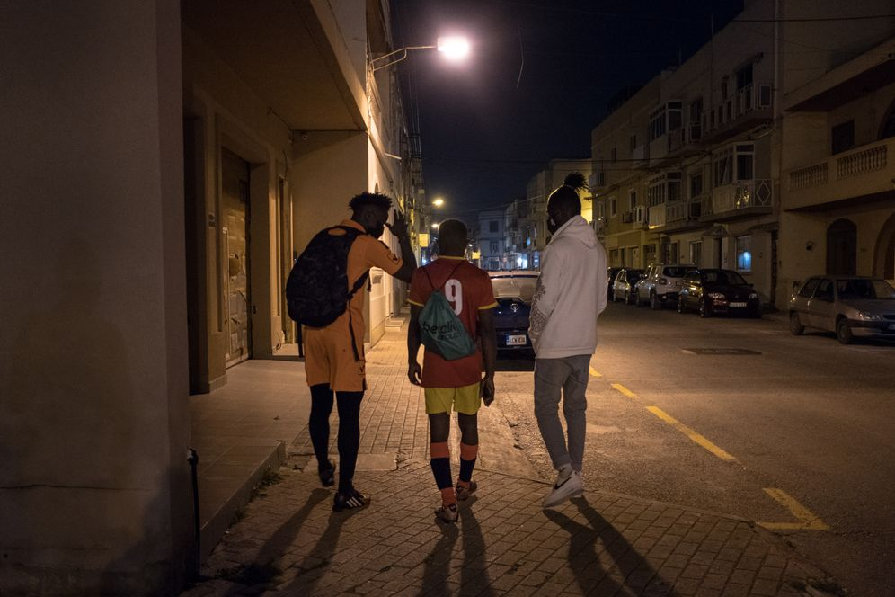The trio walking down a street in Fgura after their football match.