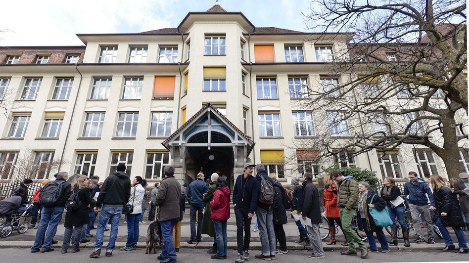 Schweizer Bürger stehen Schlange zur Stimmabgabe bei einer Volksabstimmung.