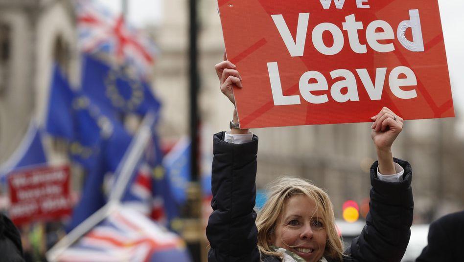 Eine Demonstrantin in London hält ein Plakat hoch