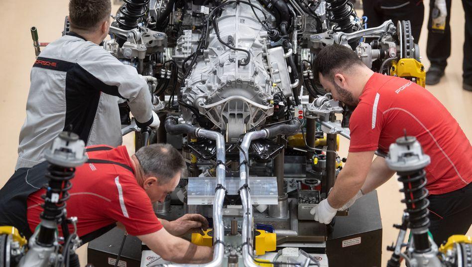 Mitarbeiter montieren den Motor eines Porsche 911