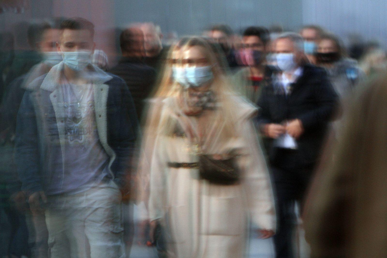 Passanten mit Mund und Nase Bedeckung spiegeln sich in einer Schaufensterscheibe in der Einkaufsstraße und Fußgängerzone