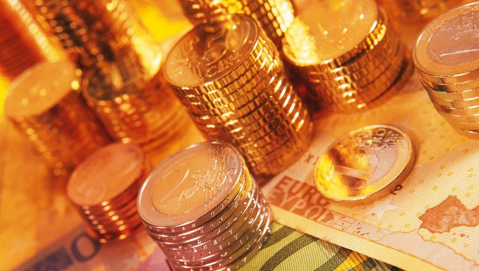 Euro-Scheine und gestapelte Münzen: Deutsche horten mehr Geld