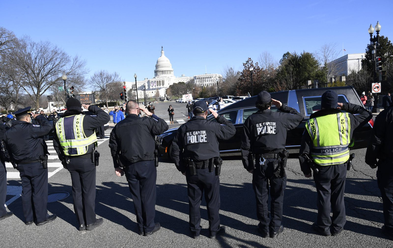 Capitol Hill police salute the passing of the funeral hearse for slain Officer Brian Sicknick, who died in the rioting