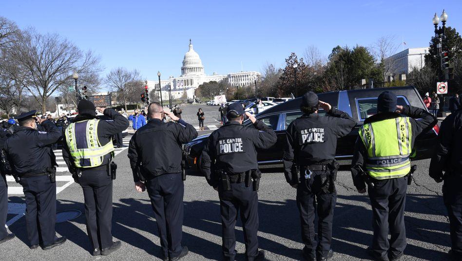 Polizisten auf dem Capitol Hill salutieren dem verstorbenen Polizisten Brian Sicknick bei der Vorbeifahrt des Leichenwagens