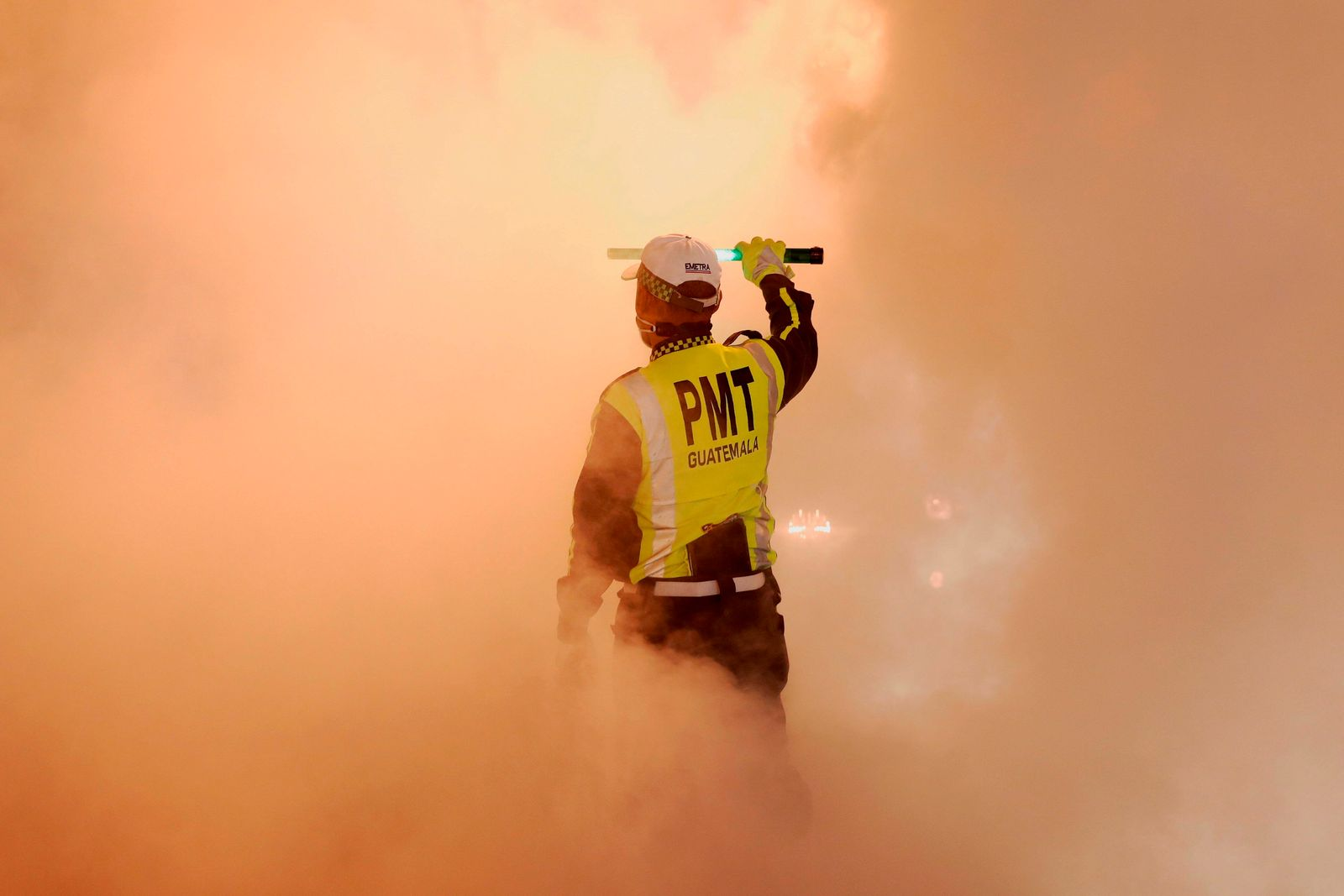 A traffic agent stops vehicles due to a cloud of disinfectant against Covid-19 spread by workers of the Municipality of