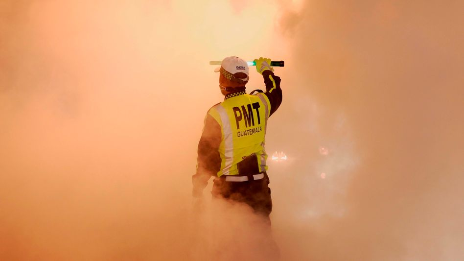 Ein Polizist desinfiziert in Guatemala Straßen. Doch viel Geld, das zur Pandemiebekämpfung eingesetzt werden sollte, hat sich durch Korruption in Luft aufgelöst – weltweit