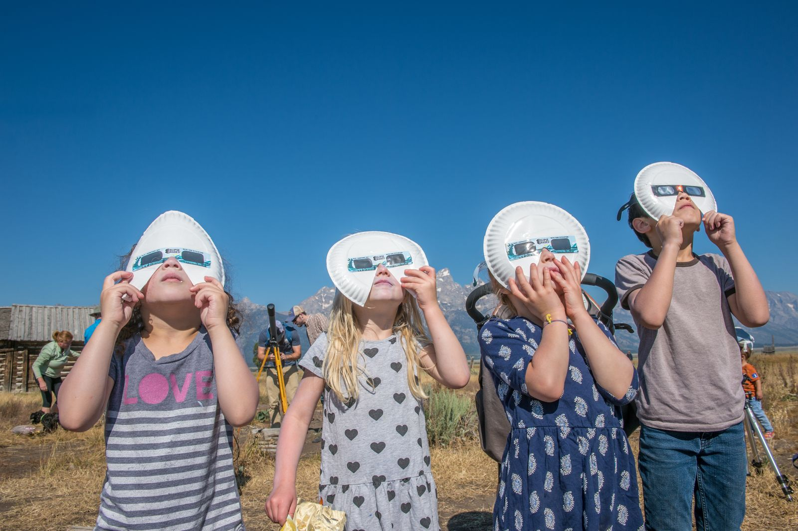Group of children look up wearing eclipse glasses to watch Solar Eclipse, Grand Tetons National Park, Teton County, Wyoming