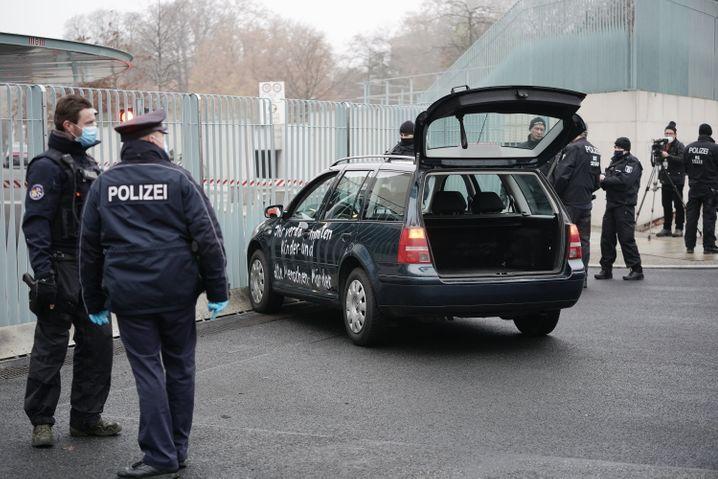 Polizisten neben dem mit einer Beschimpfung beschmierten Fahrzeug