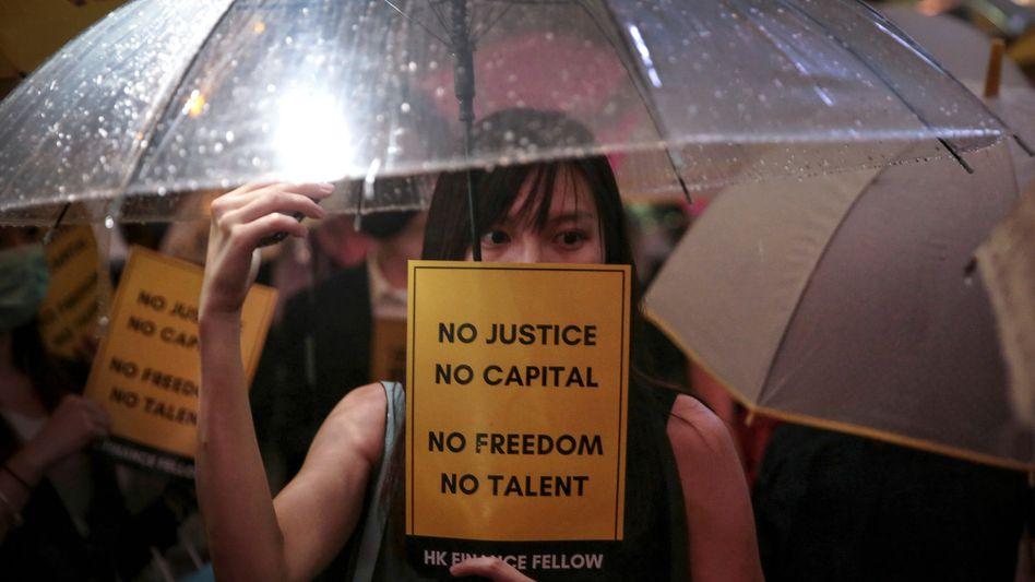Eine Demonstrantin in Hongkong protestiert unter einem Regenschirm gegen die Regierung