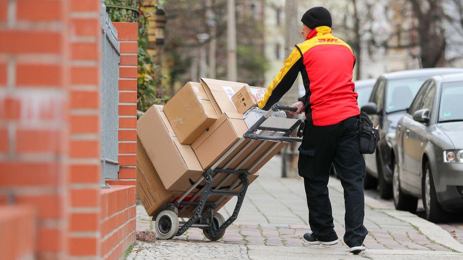 Ein DHL-Bote liefert einen Stapel Pakete aus