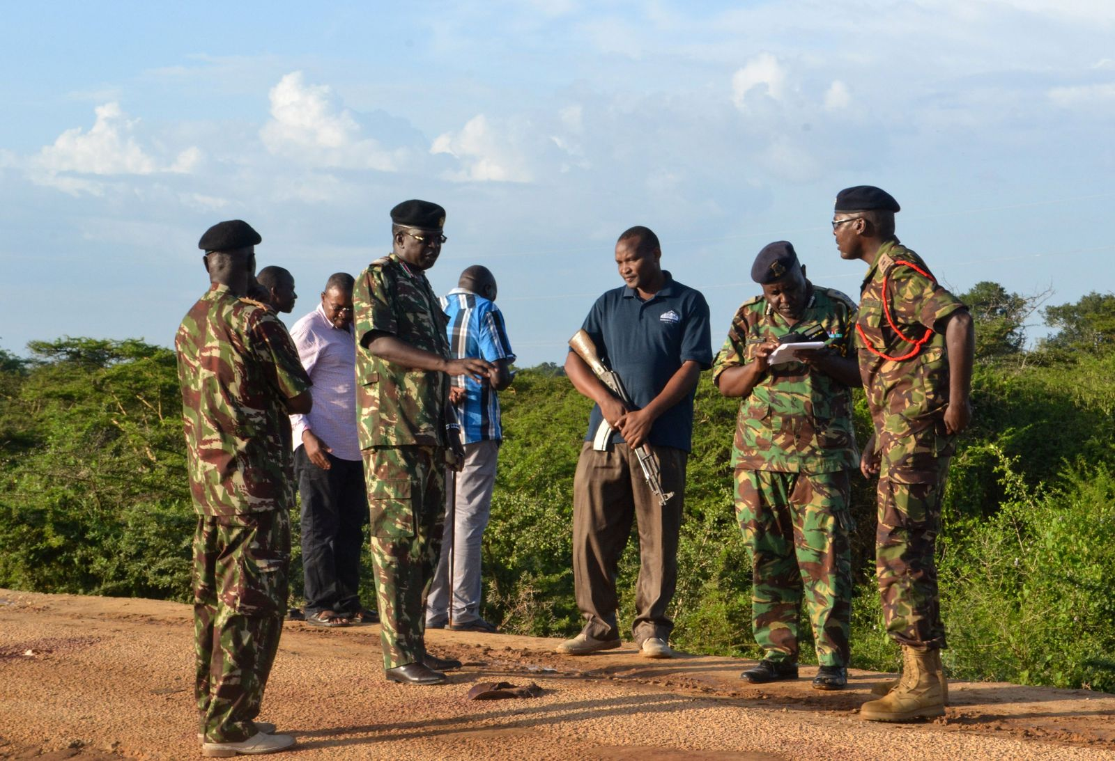 Kenyan police officers are seen near the scene where armed assailants killed three people and injured two others in Nyongoro area of Lamu county