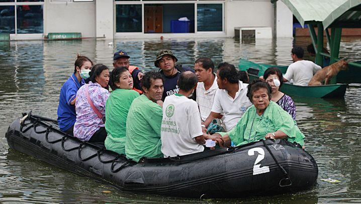 Flut in Thailand: Per Auto und Boot aus den Wassermassen