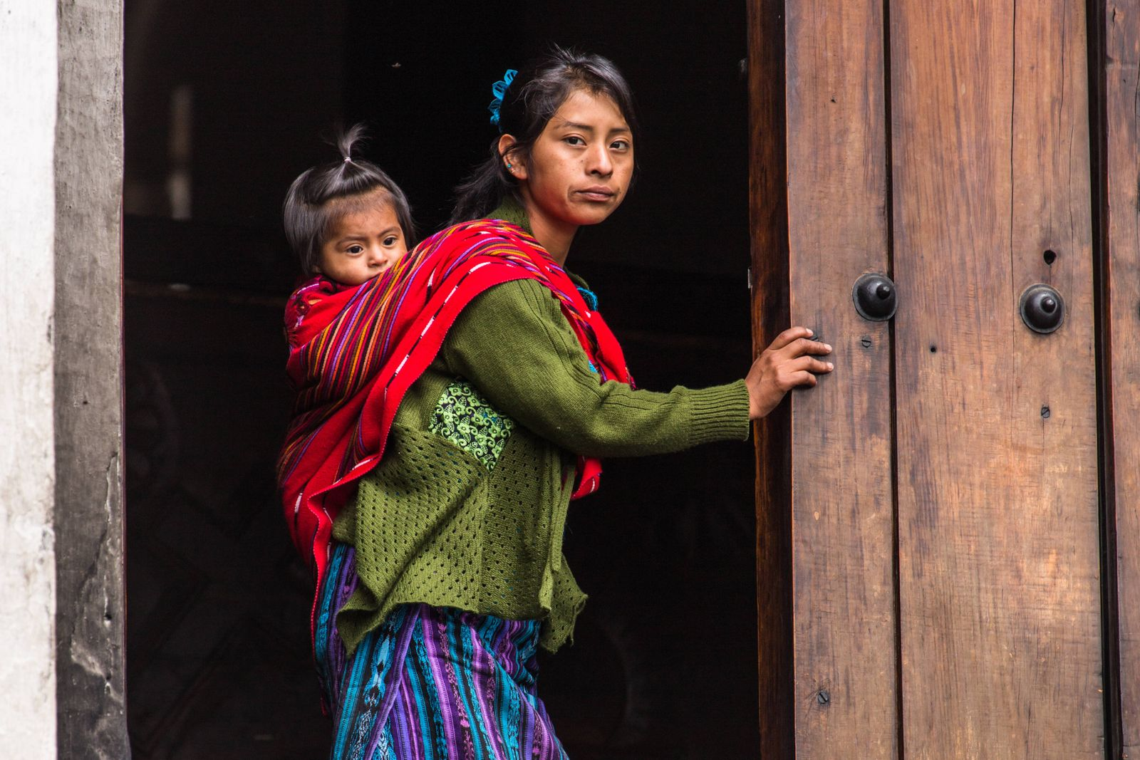 A young Quiche Mayan woman, in traditional dress, and her daughter stand in the door of the Church of Santo Tomas in Chi