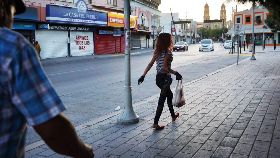 Eine Frau läuft durch die Innenstadt der Grenzstadt Ciudad Juárez, in der immer wieder Frauen entführt werden. In der Coronakrise ist das Zentrum verwaist.