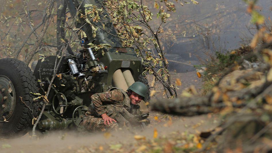 Ein armenischer Soldat feuert an der Front eine Artilleriewaffe ab