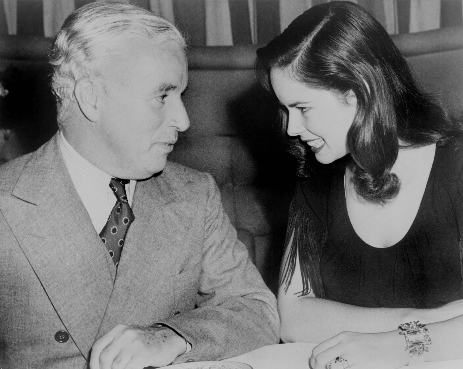 Charlie Chaplin (1889-1977) sitting with his young wife Oona at Hollywood nightclub in 1944. The couple married the prev