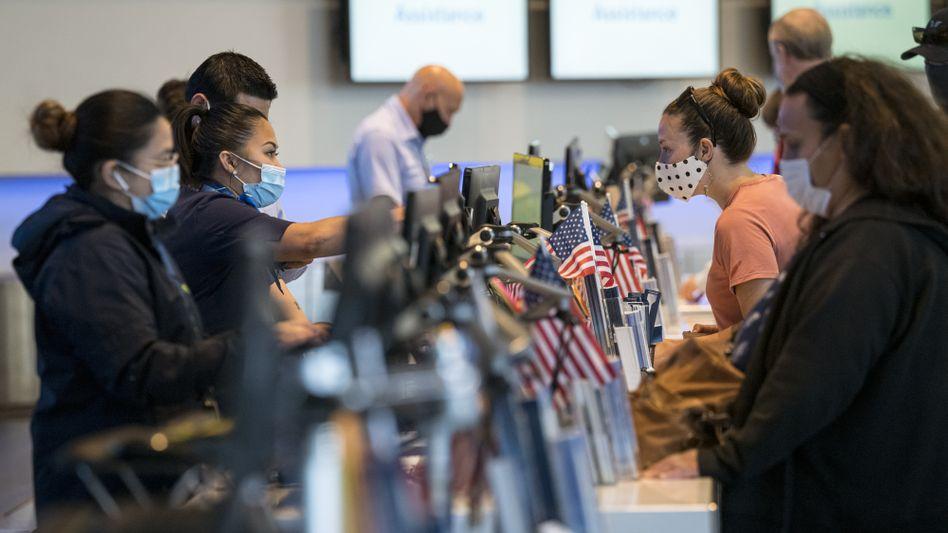 Flugpassagiere mit Mund-Nasen-Schutz checken am San Francisco International Airport ein