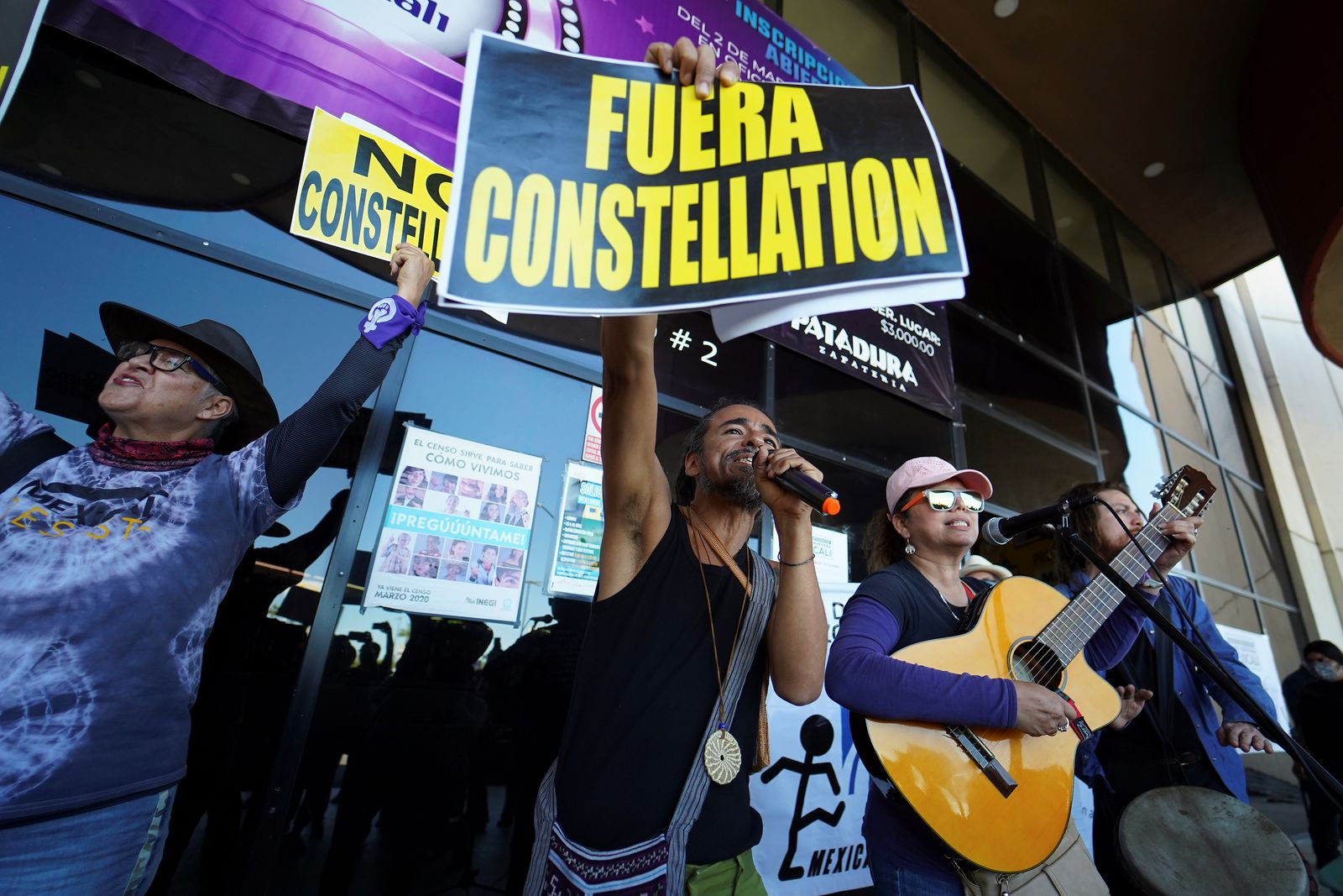"""Singer Ruben Albarran of the Mexican band Cafe Tacuba holds a sign reading """"Constellation Out"""" during a public consultation to ask whether to let U.S. company Constellation Brands Inc, open a massive brewery in northern Mexico, in Mexicali"""