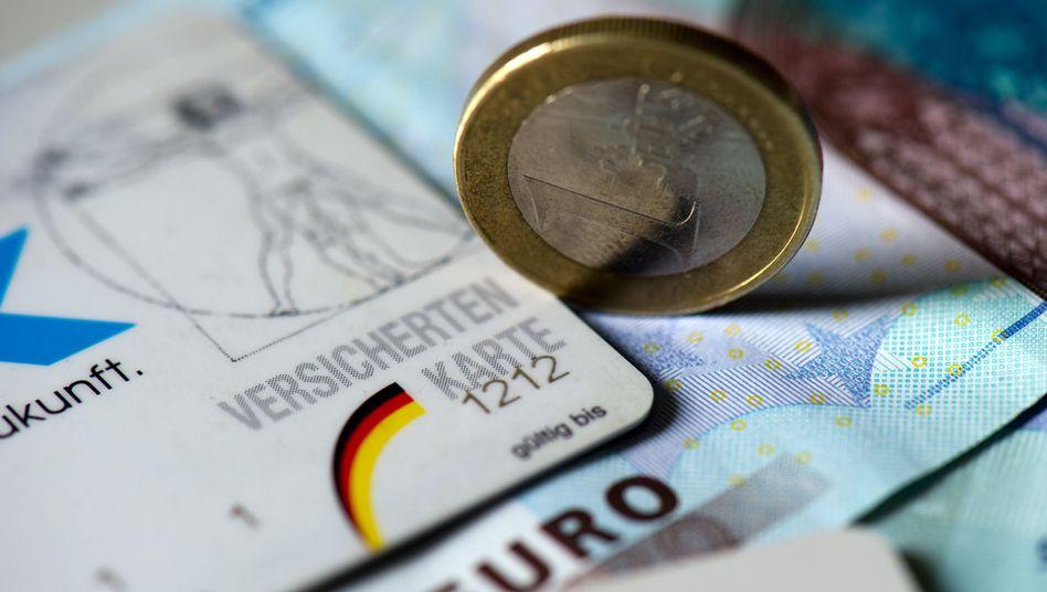 Geld neben Versichertenkarte: Schulden bei der Krankenkasse sorgen für Ärger