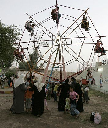 Residents ride in a ferris wheel in al-Numan Square park in northern Baghdad's Adhamiya district.