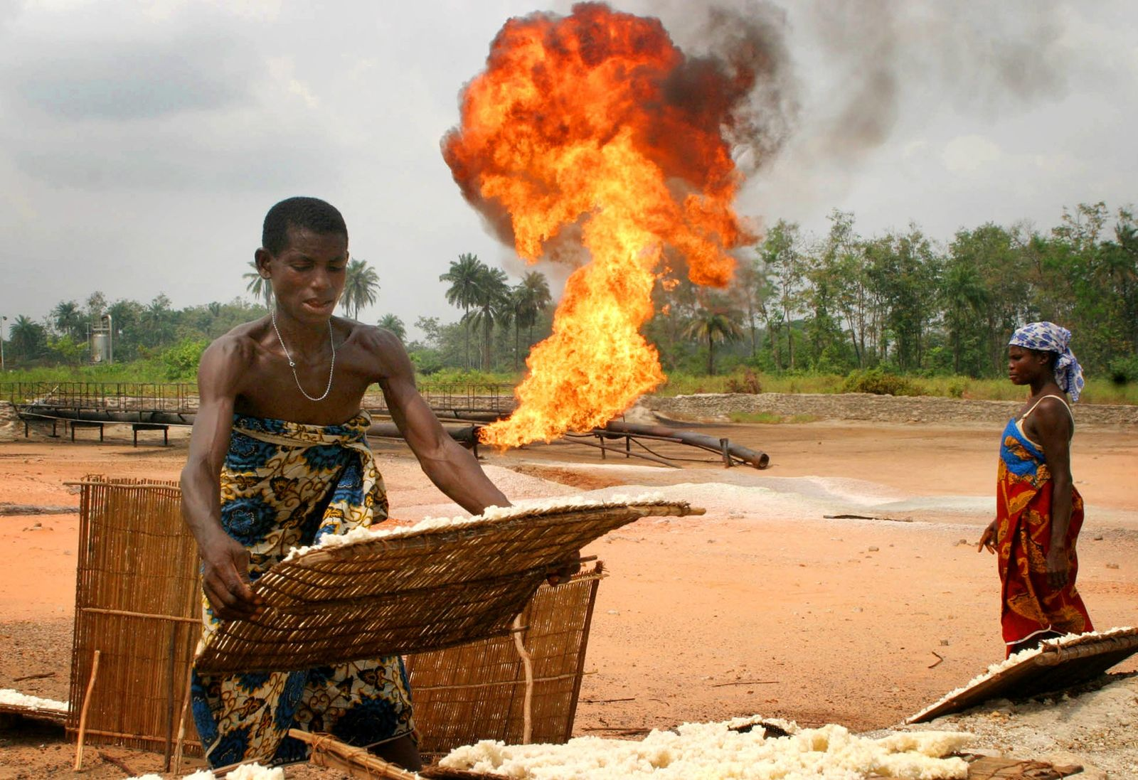 A woman dries cassava beside flames from an oil flowstation in Nigeria
