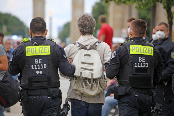 Zwei Polizisten führen einen Demonstranten bei der verbotenen »Querdenker«-Demo ab