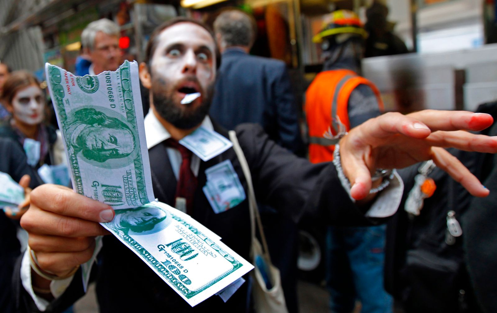"A demonstrator, dressed as a ""corporate zombie"" walks with others taking part in an Occupy Wall Street protest in lower Manhattan in New York"