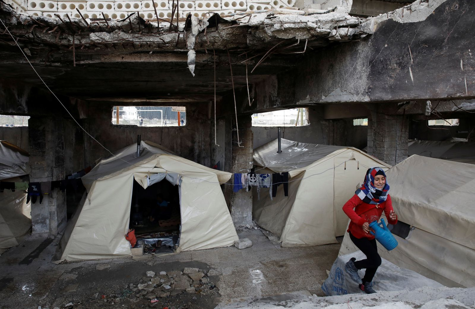 FILE PHOTO: An internally displaced Syrian girl steps up the stairs in an IDP camp located in Idlib