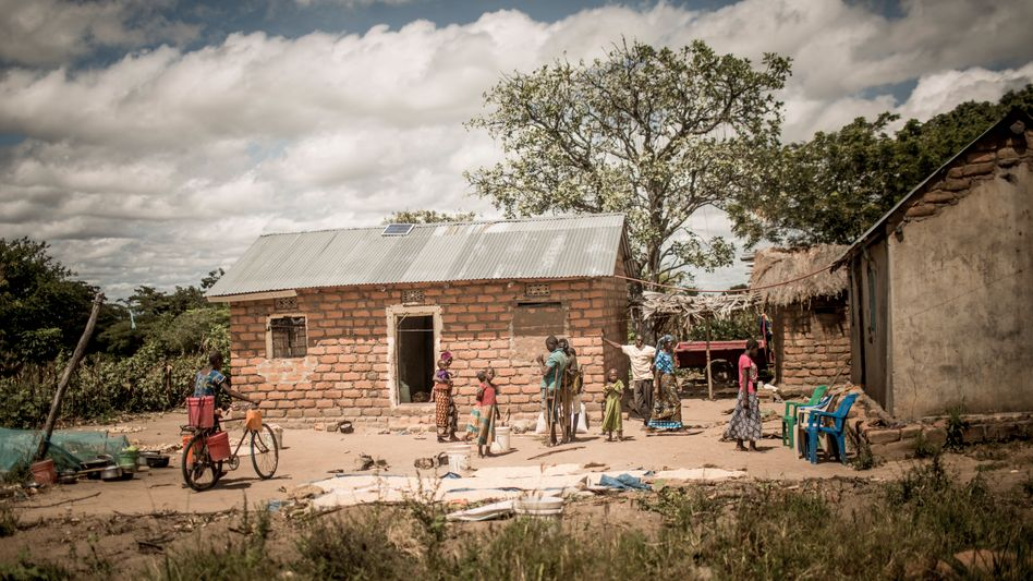 In the Tanzanian village of Mbola, clay brick walls and corrugated iron roofs are a sign of relative prosperity. Many families still live in thatched huts.