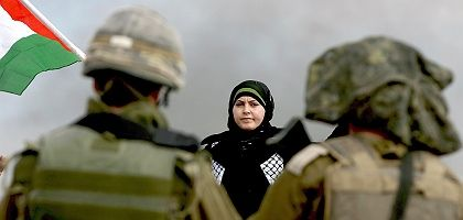 A Palestinian woman confronts two Israeli soldiers during a protest in the West Bank town of Billin.