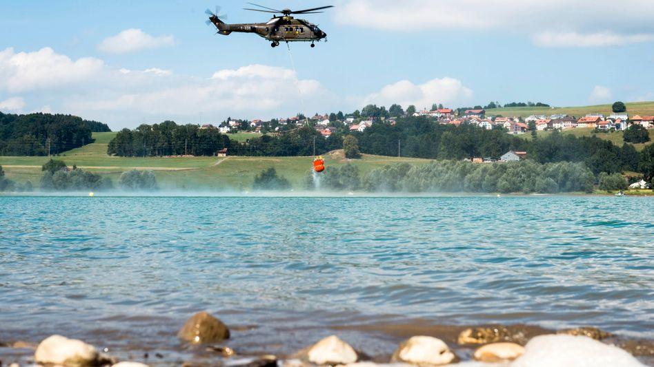 """Ein Schweizer """"Super Puma"""" tankt Wasser, hier allerdings über einem Schweizer See"""