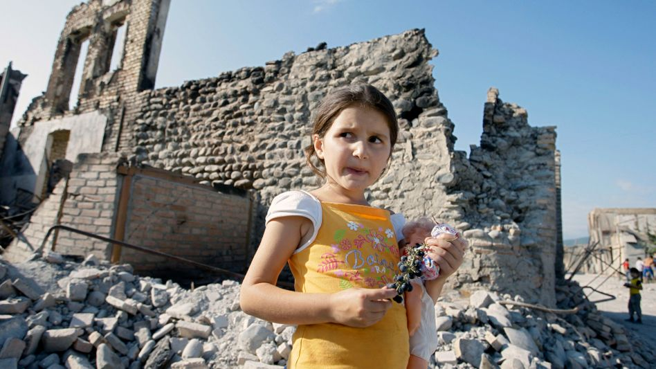 In this Sept. 4, 2008 photo, a girl plays near a ruined building in Tskhinvali.