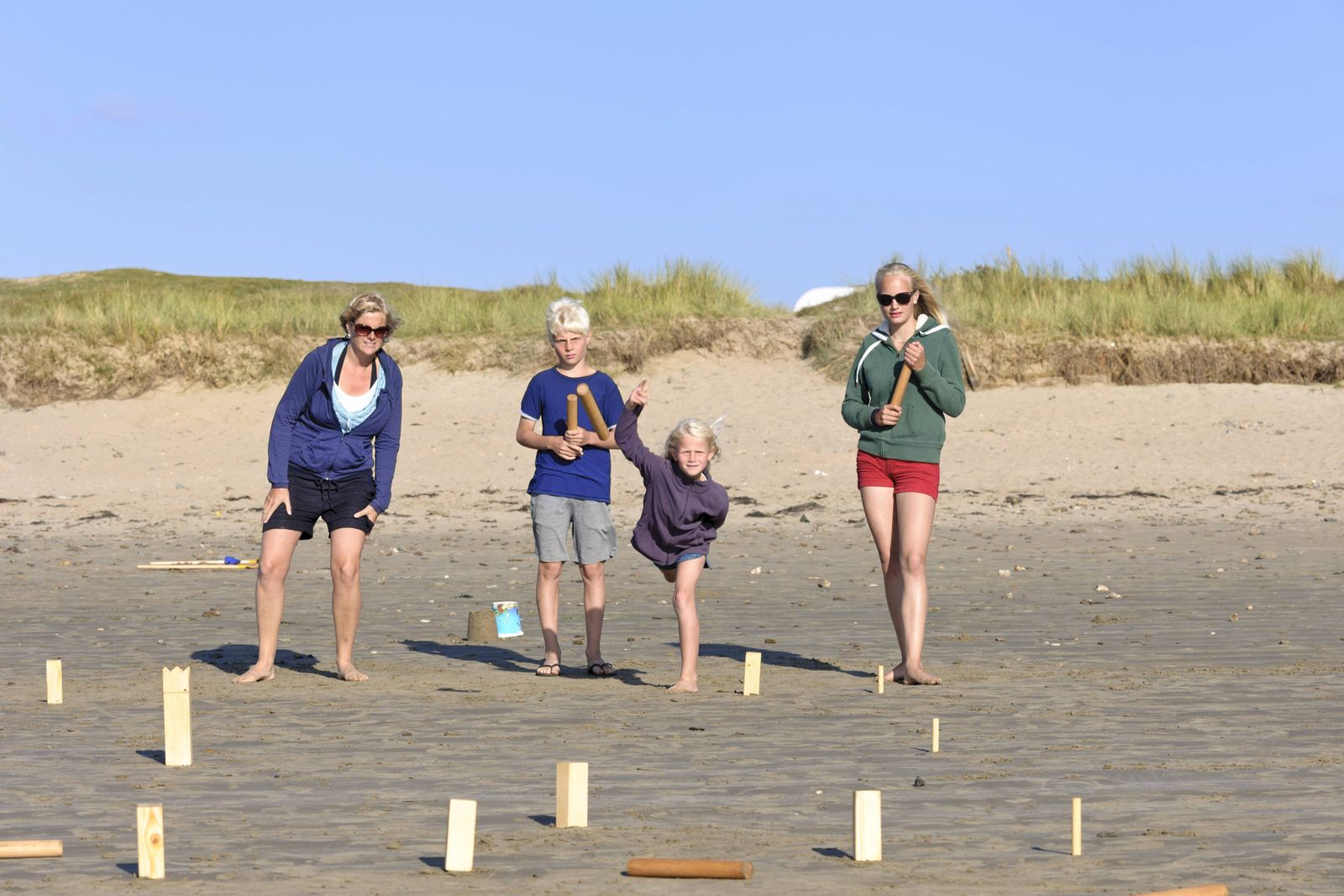 Mother and three children playing Kubb on the beach model released Symbolfoto PUBLICATIONxINxGERxSUI